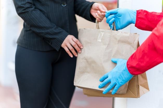Donne che lavorano tenendo il sacchetto di carta con cibo da asporto, consegna a domicilio, da asporto