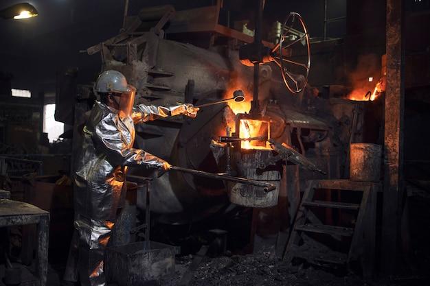 Operaio in tuta antincendio e elmetto protettivo che controlla il processo di fusione del ferro nel forno per fonderia.