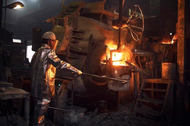 Operaio in tuta di protezione termica versando metallo liquido nel secchio.