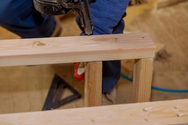 Gli operai che utilizzano una pistola sparachiodi pneumatica installano travi in legno sulla nuova casa in costruzione
