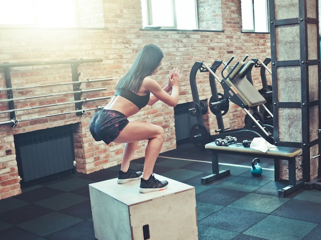 Concetto di allenamento. donna castana in abiti sportivi si accovaccia su una scatola di legno in palestra. vista posteriore. allenamento funzionale