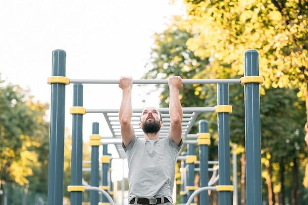 Uomo di esercizio di allenamento pull up stile di vita atletico