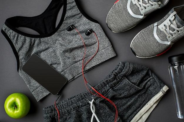 Piano di allenamento con cibo e attrezzature per il fitness su sfondo grigio vista dall'alto