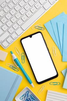 Composizione sul posto di lavoro su sfondo giallo con telefono vuoto