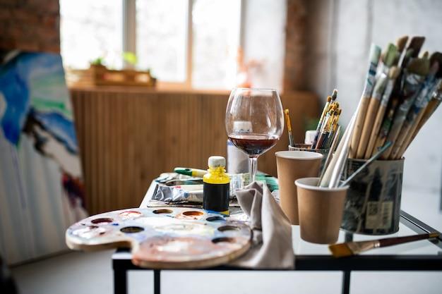 Luogo di lavoro del pittore professionista contemporaneo con tavolozza, vari pennelli e altre attrezzature sul tavolo