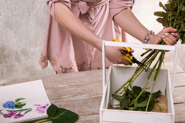 Luogo di lavoro di decoratore, fiorista. schizzo di fiore. attrezzi professionali. tavolo in legno da laboratorio di floristica con decoro. opera d'arte decorativa ad acquerello