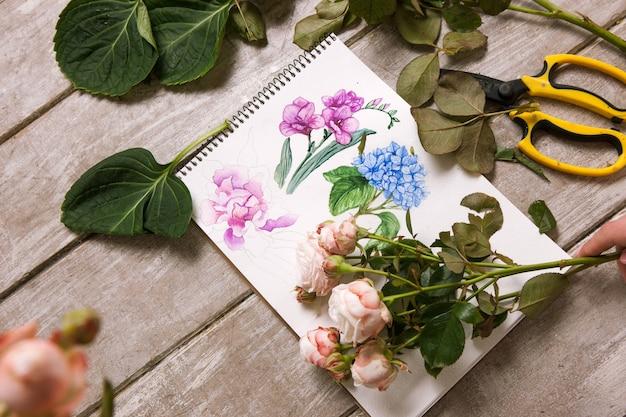 Luogo di lavoro di decoratore, fiorista. schizzo della vista dall'alto del fiore. attrezzi professionali. tavolo in legno da laboratorio di floristica con decoro. opera d'arte decorativa ad acquerello