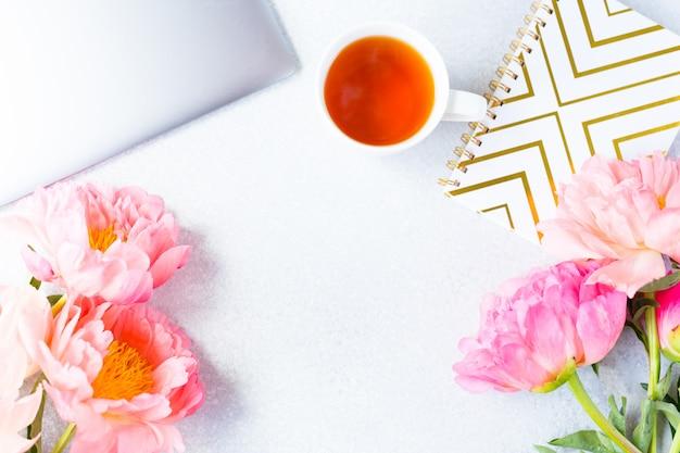 Luogo di lavoro, visualizzazione desktop. computer portatile, peonia rosa, tazza di tè. area di lavoro della donna.