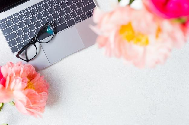 Luogo di lavoro, visualizzazione desktop. computer portatile, peonia rosa e vetri su bianco