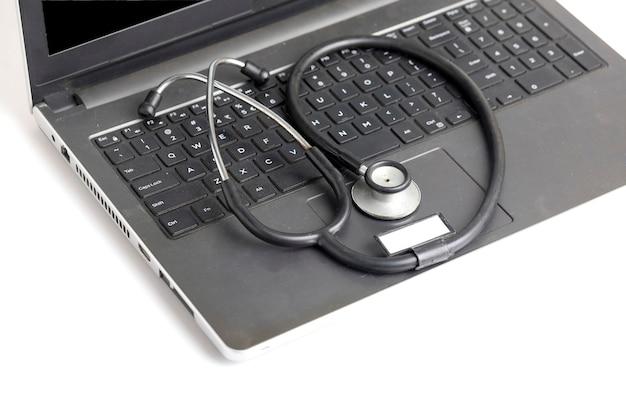 Posto di lavoro del medico con laptop e stetoscopio su sfondo bianco