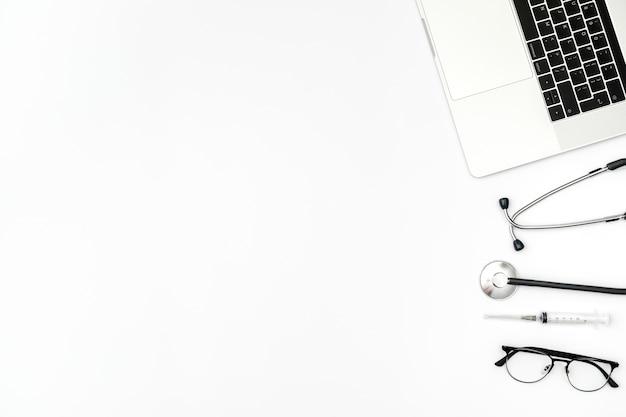 Luogo di lavoro del medico con il computer portatile e lo stetoscopio sul tavolo bianco
