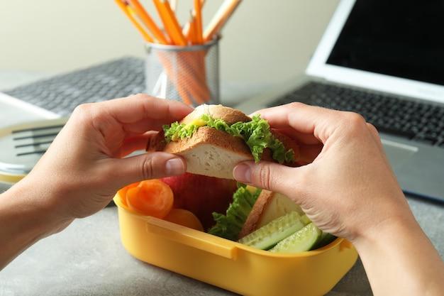 Il posto di lavoro che mangia con le mani femminili tiene il panino, primo piano