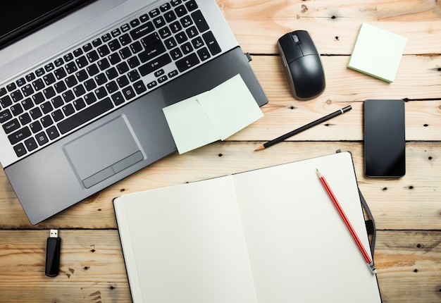 Luogo di lavoro, laptop e blocco note sulla tavola di legno