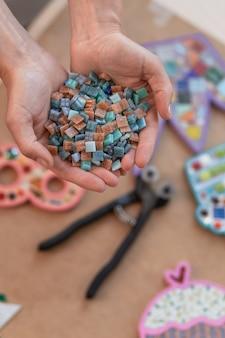 Luogo di lavoro del maestro mosaicista: le mani delle donne che tengono i dettagli del mosaico nel processo di creazione di un mosaico