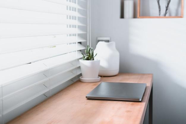 Posto di lavoro vicino alla finestra con laptop e computer. copia spazio