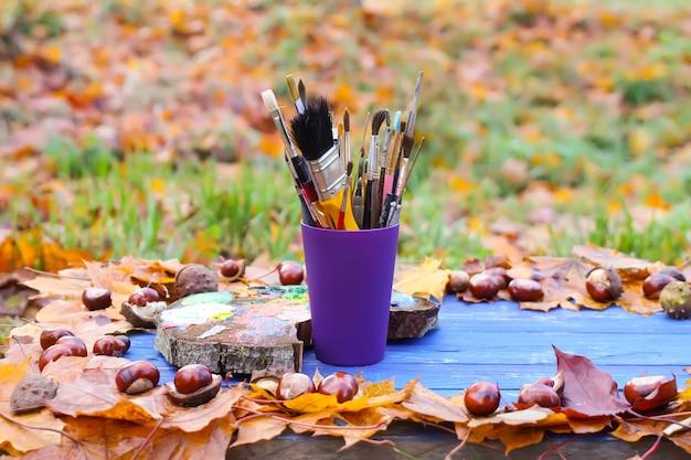 Posto di lavoro per pittore nel parco autunnale con tavolozza di legno e pennelli in contenitore di plastica. foglie di autunno e castagne su fondo di legno blu.