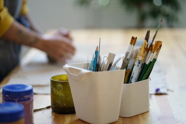 Posto di lavoro di ciotole di pennelli per decorare le ceramiche per colorare le stoviglie di argilla nel laboratorio di studio