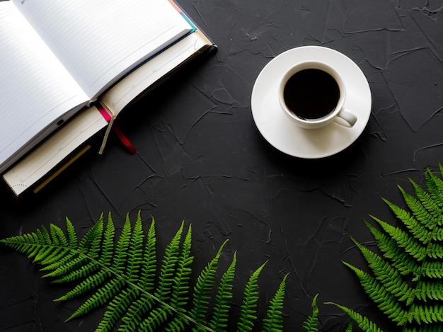 Posto di lavoro con tazza di caffè, diario e foglie