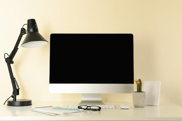 Posto di lavoro con computer desktop contro il beige