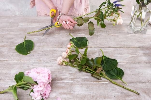 Posto di lavoro con fiori. mani di fiorista. fondo di legno della tavola del laboratorio di floristica. opera d'arte decorativa dal fiore di primavera