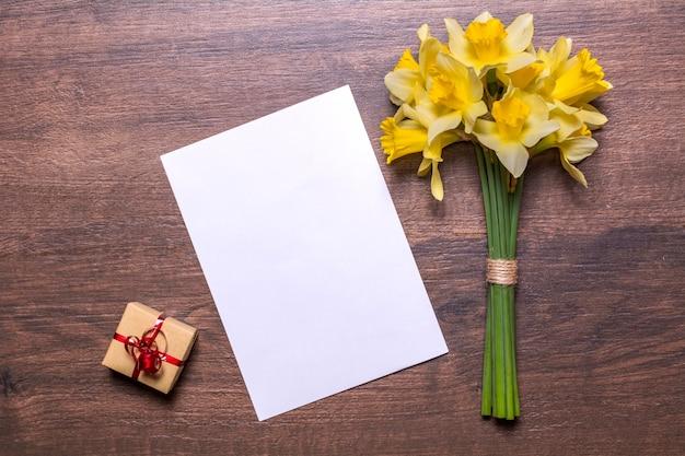 Luogo di lavoro con un regalo con un nastro rosso, un pezzo di carta e un bouquet di narcisi su uno sfondo di legno. design piatto laici, vista dall'alto.