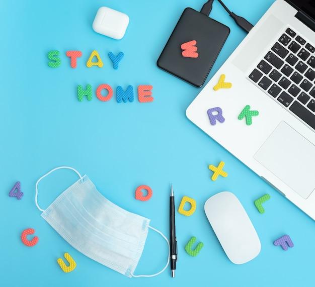 Posto di lavoro con laptop, auricolari, mouse, matita, lettere e maschera protettiva medica