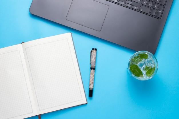 Posto di lavoro con computer portatile, una bevanda fresca con ghiaccio e menta, un diario aperto su un blu. il concetto dell'area di lavoro di un giornalista, scrittore, libero professionista, copywriter. vista piana, vista dall'alto
