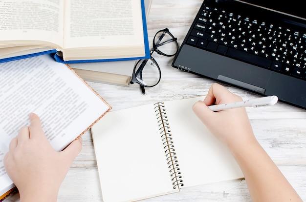 Luogo di lavoro con computer portatile, blocco note, penna e libri
