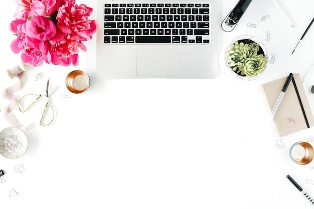 Posto di lavoro con laptop succulente peonie rocchetto di forbici dorate con nastro beige matite e diario composizione piatta per blog vista dall'alto