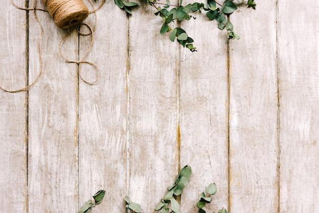 Posto di lavoro con ornamento di alloro disteso piatto. tavolo in legno da laboratorio di floristica con decoro. opera d'arte decorativa dal fiore di primavera