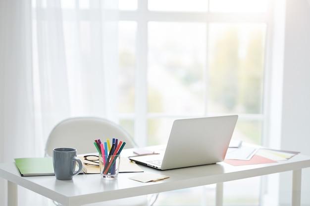 Posto di lavoro con laptop bianco, note e tazza di tè sul tavolo di casa. luce intensa proveniente dalla finestra. concetto di design d'interni