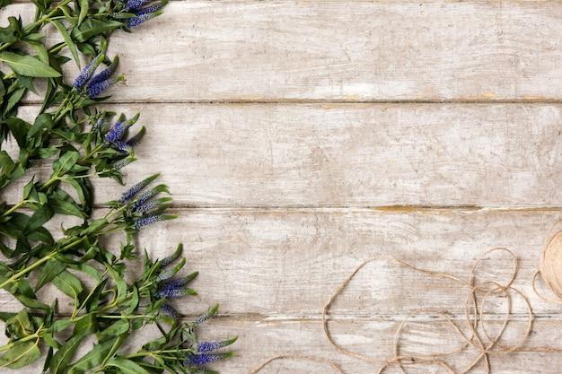 Posto di lavoro con decorazioni di fiori di campo piatta. tavolo in legno da laboratorio di floristica con decoro. opera d'arte decorativa dal fiore di primavera