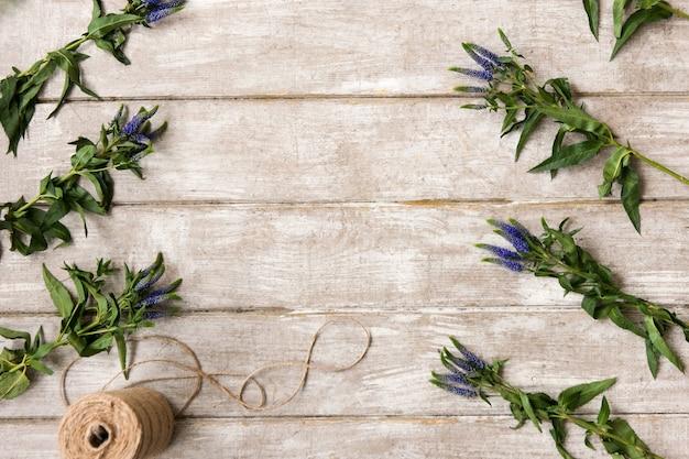 Posto di lavoro con ornamento di fiori di campo piatto. tavolo in legno da laboratorio di floristica con decoro. opera d'arte decorativa dal fiore di primavera