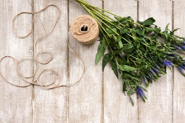 Posto di lavoro con fiori di campo e corda piatta. tavolo in legno da laboratorio di floristica con decoro. opera d'arte decorativa dal fiore di primavera