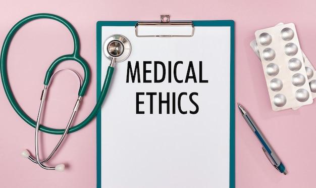 Foglio di lavoro con l'iscrizione etica medica, stetoscopio e pillole, vista dall'alto