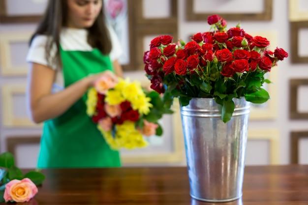 Fiorista per officina, realizzazione di mazzi di fiori e composizioni floreali. donna che raccoglie un mazzo di fiori