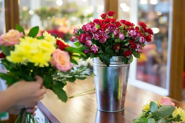 Laboratorio di fiorista, realizzazione bouquet e addobbi floreali. donna che raccoglie un mazzo di fiori