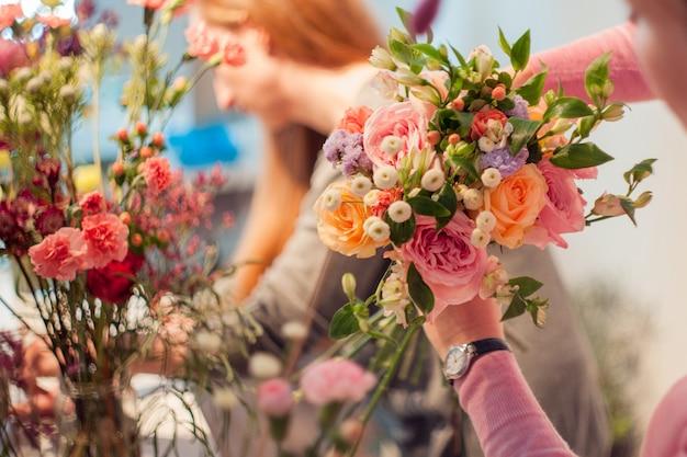 Fiorista per officina, realizzazione di mazzi di fiori e composizioni floreali. donna che raccoglie un mazzo di rose. focalizzazione morbida