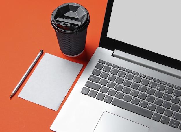 Concetto minimo di spazio di lavoro. taccuino, foglio di carta con una matita, contenitore di cartone di caffè sul tavolo arancione