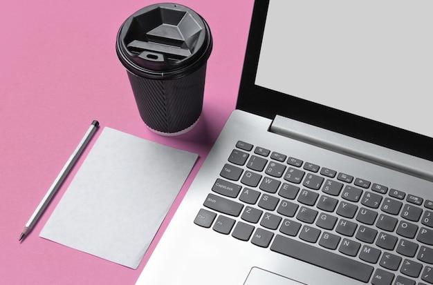 Concetto minimo di area di lavoro. notebook, foglio di carta con una matita, contenitore di cartone di caffè su sfondo rosa pastello