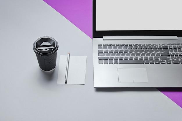 Concetto minimo di spazio di lavoro. taccuino, foglio di carta con una matita, contenitore di cartone di caffè sul tavolo grigio viola