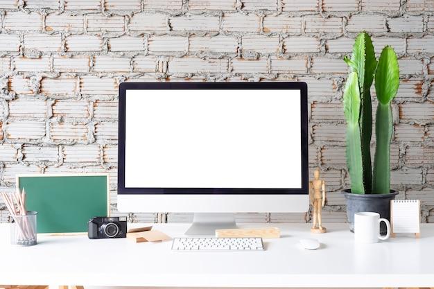 Area di lavoro mockup computer con tazza da caffè, barattolo di matita e blocco note sul tavolo bianco