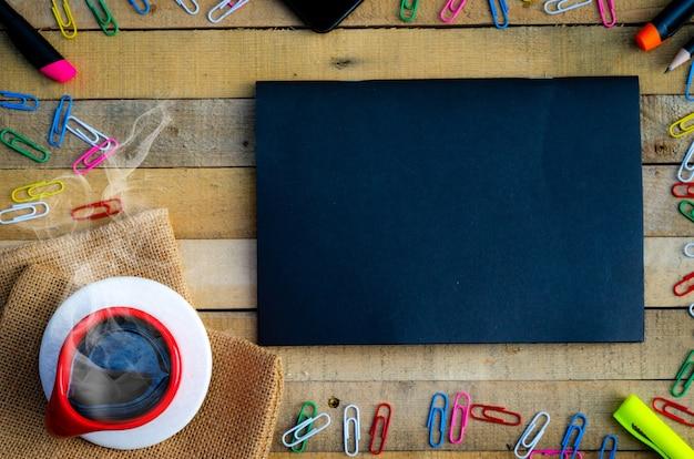 Mockup dell'area di lavoro su un tavolo in legno, tazza di caffè e forniture