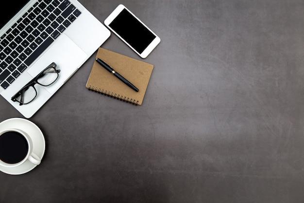 Area di lavoro in ufficio, scrivania nera con quaderno bianco e altre forniture per ufficio.