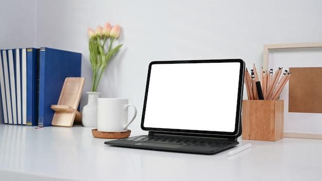 Area di lavoro con tablet computer, tazza di caffè, libri e articoli per ufficio sul tavolo bianco.