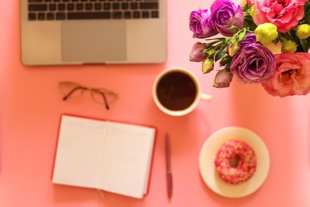 Area di lavoro con fiori, laptop, ciambelle e caffè