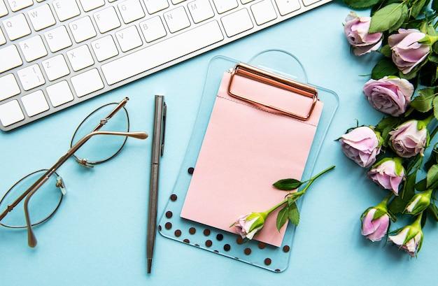 Area di lavoro con tastiera, appunti, rose su sfondo blu pastello. scrivania da ufficio. sfondo femminile vista dall'alto. vista piana laico e dall'alto.