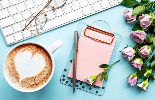 Area di lavoro con tastiera, appunti, rose su sfondo blu pastello. scrivania da ufficio. sfondo femminile vista dall'alto. vista piana, vista dall'alto.