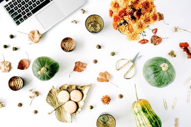Area di lavoro con laptop, bouquet di crisantemi, zucca, foglie, forbici su bianco