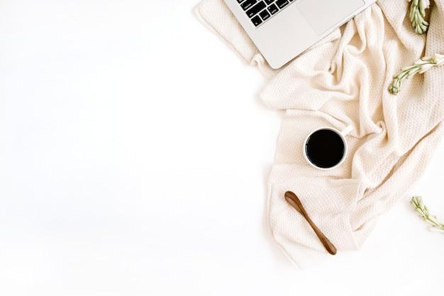 Area di lavoro con laptop, caffè, cucchiaio, fiori bianchi e tessuto beige su superficie bianca
